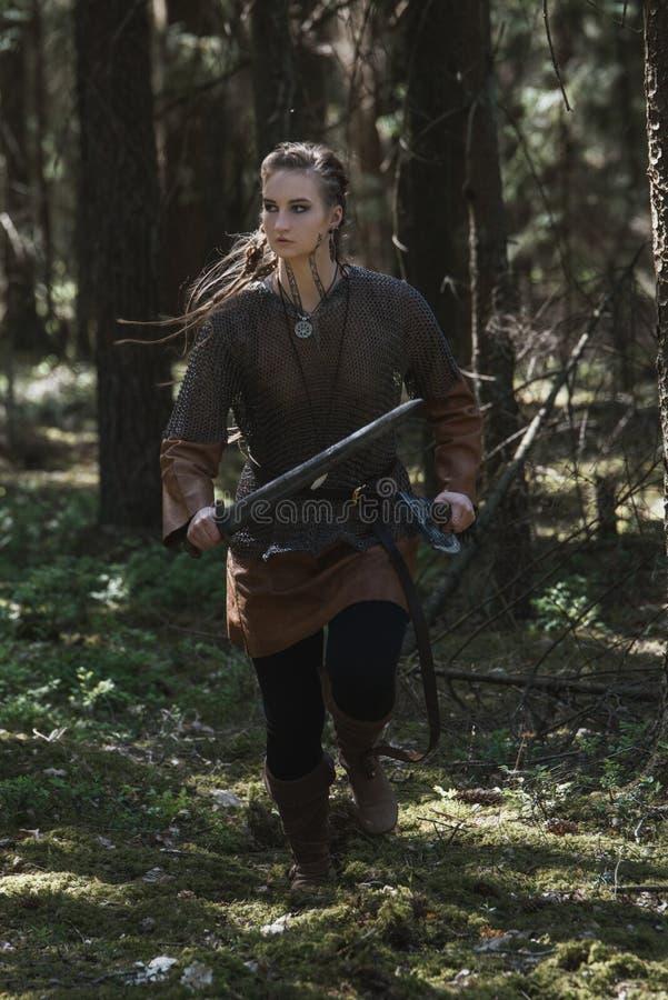 La femme de Viking avec l'épée et le marteau portant le guerrier traditionnel vêtx d'une forêt mystérieuse profonde photos stock