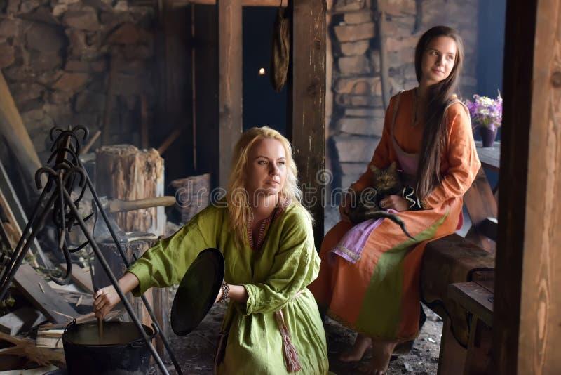 La femme de Viking prépare la nourriture dans le pot sur le feu photo libre de droits