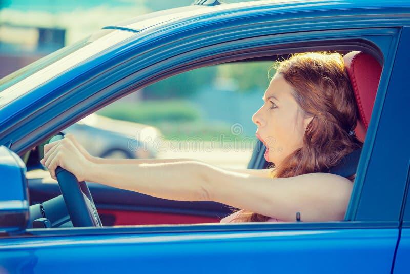 La femme de visage d'effroi conduisant la bouche grande ouverte de voiture observe des cris images stock