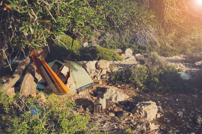 La femme de voyageur détend dans un hamac sur un bord de la mer rocheux photographie stock