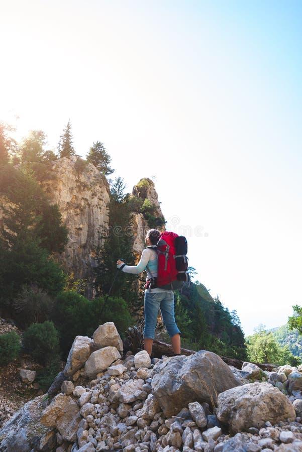 La femme de voyageur se tient sur la pierre photographie stock libre de droits
