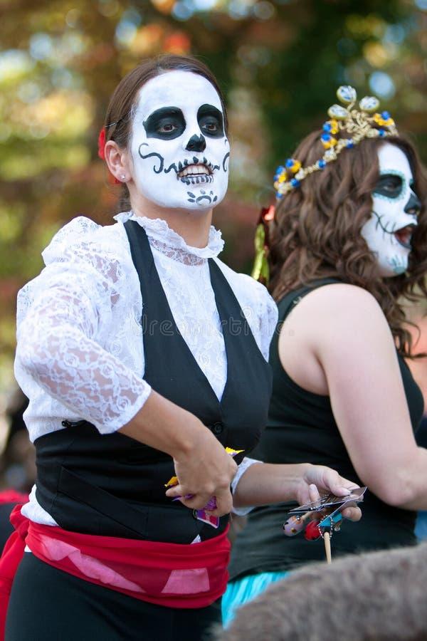 La femme de zombi jette la sucrerie en l'air pour se serrer au défilé de Halloween photographie stock libre de droits