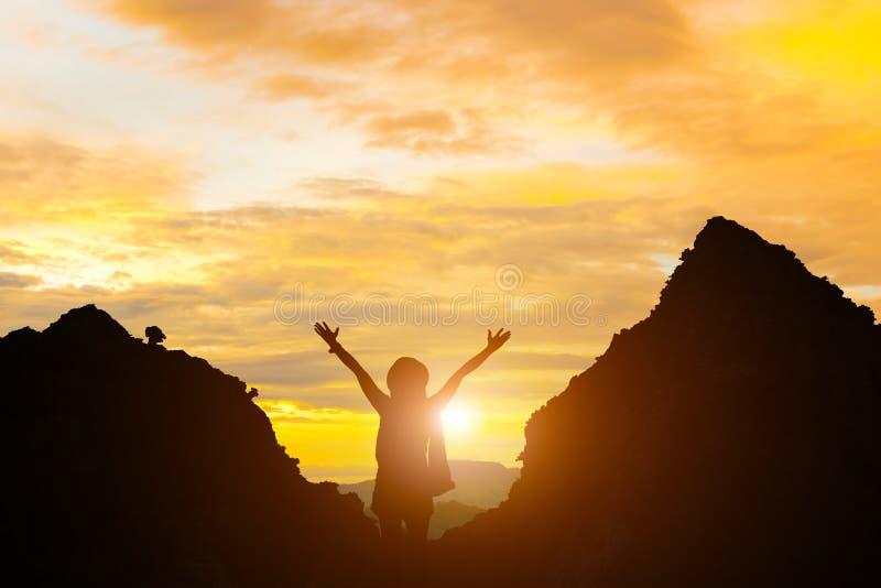 La femme debout tenant la fille de silhouette du soleil et de montagne de soirée de main se tiennent images stock