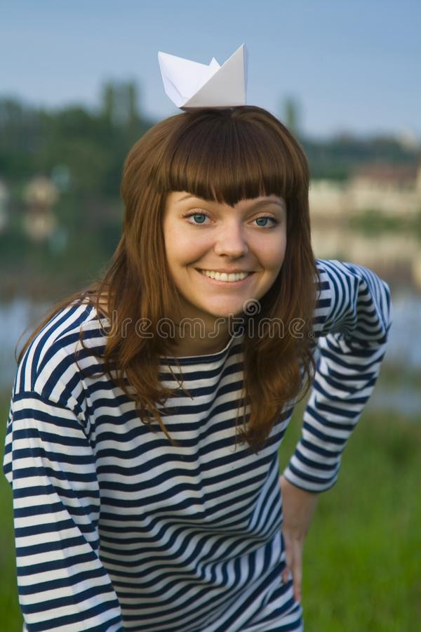 La femme a dedans dépouillé t-court avec le bateau de papier sur sa tête photos stock