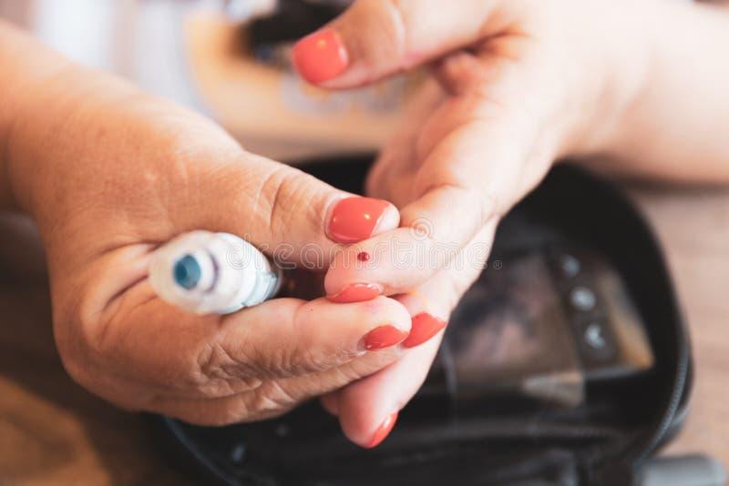 La femme dessine le sang après utilisation d'une aiguille pour examiner le niveau de glucose avec un glucometer images stock