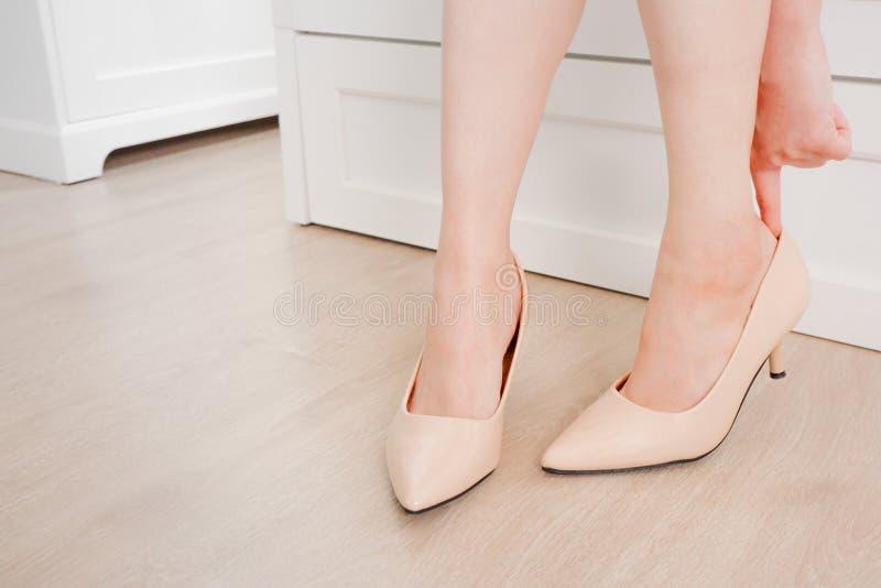La femme deux mince portant les sandales beiges d'été de chaussures s'asseyent sur le sofa et le fond en bois de plancher Belle j photo stock