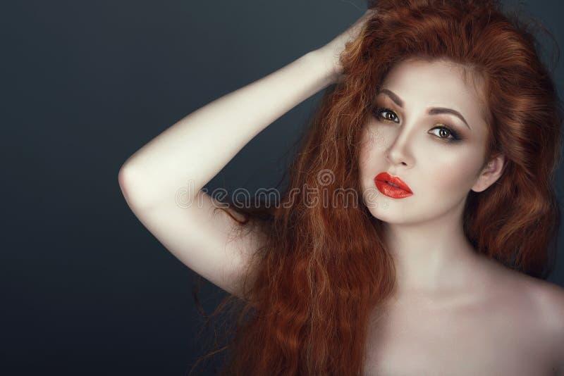 La femme dirigée rouge magnifique avec beau composent tenir sa main dans ses cheveux photo libre de droits