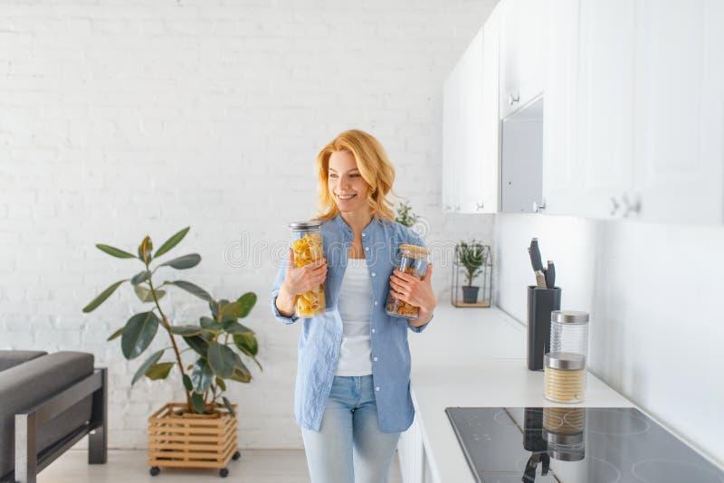 La femme dispose à faire cuire le petit déjeuner sur la cuisine photos stock