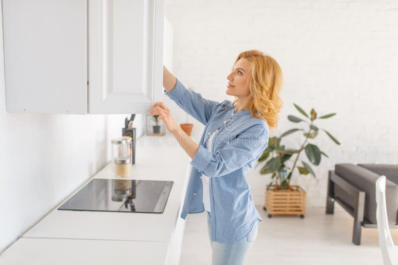 La femme dispose à faire cuire le petit déjeuner sur la cuisine photographie stock libre de droits
