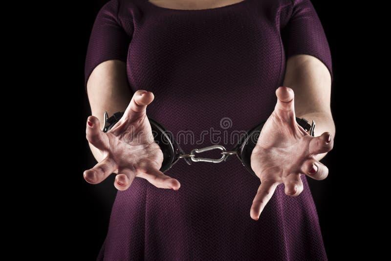 La femme docile portant une robe pourpre en cuir menotte dessus photos stock