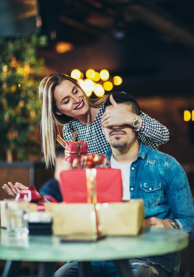 La femme donne un cadeau à un jeune homme dans le café images stock