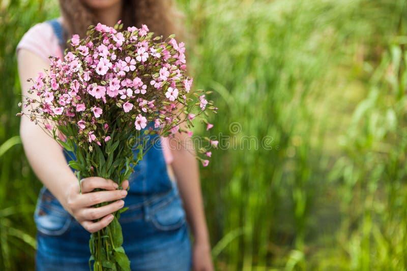 La femme donnent les fleurs roses comme cadeau, avec l'espace de copie comme fond image libre de droits