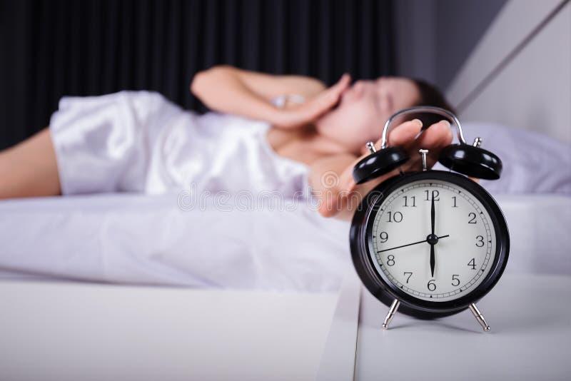 La femme dormant et se réveillent pour arrêter le réveil dans le mornin photographie stock libre de droits