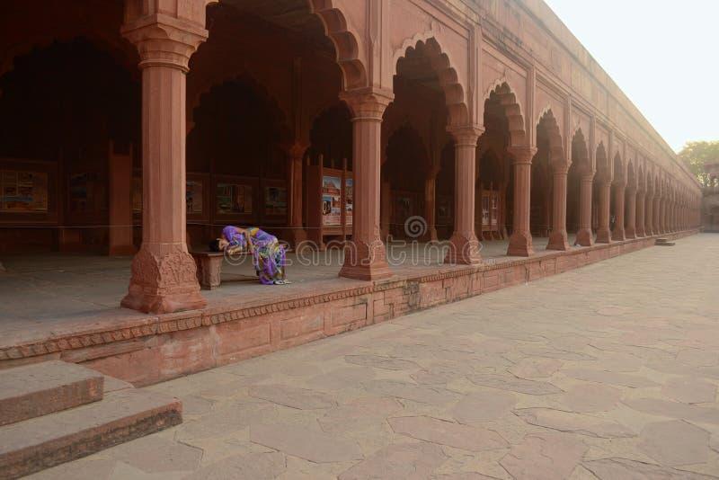 La femme dort sur un banc en complexe de Taj Mahal images stock