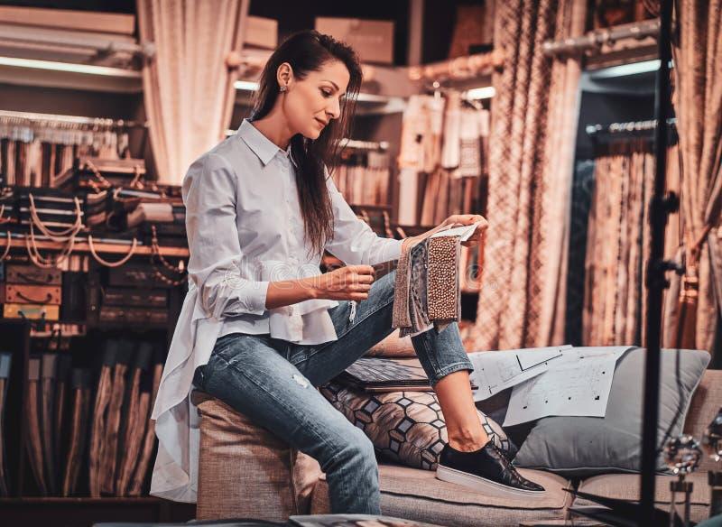 La femme douée diligente s'assied sur le sofa à son studio de vêtement avec des dessins photographie stock