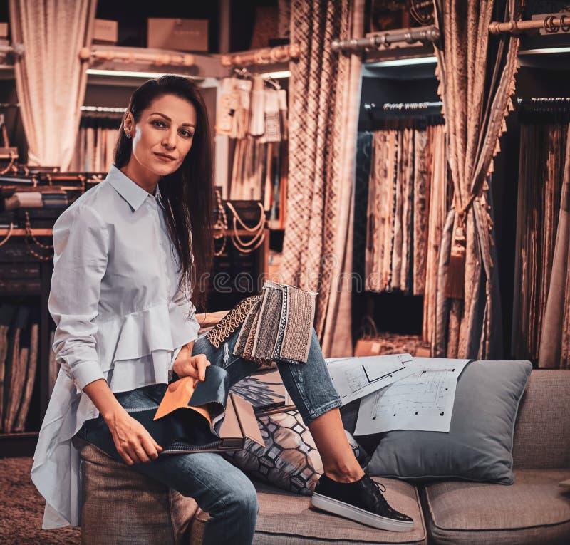 La femme douée diligente s'assied sur le sofa à son studio de vêtement avec des dessins photo stock