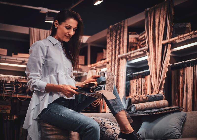 La femme douée diligente s'assied sur le sofa à son studio de vêtement avec des dessins photos stock