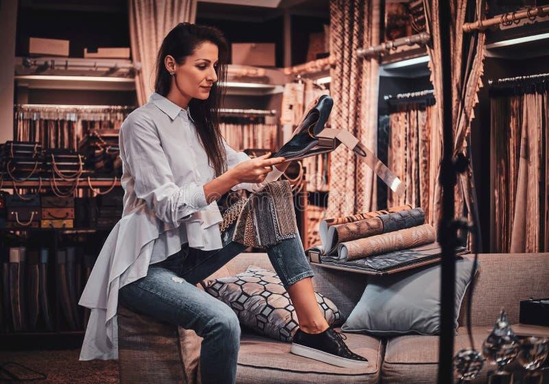 La femme douée diligente s'assied sur le sofa à son studio de vêtement avec des dessins images stock