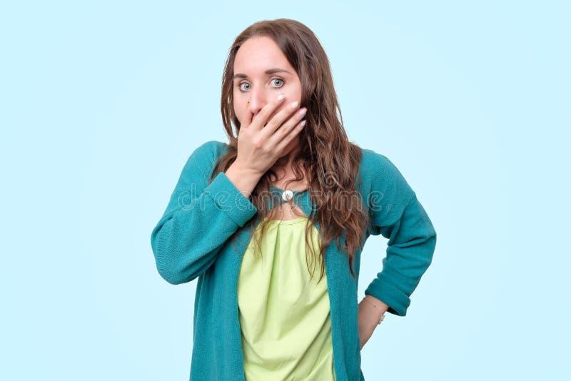 La femme drôle est choquée avec des nouvelles couvrant sa bouche dans la panique photos libres de droits