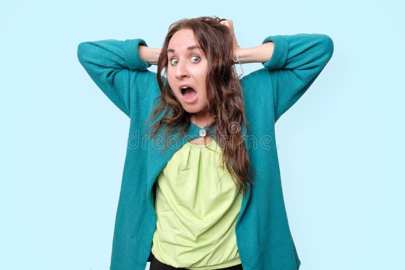 La femme drôle est choquée avec des nouvelles tenant la tête avec des mains dans la panique photo stock