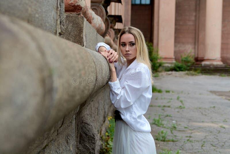 La femme du regard de mode Portrait moderne de jeune femme Jeune femme habill?e dans la jupe blanche et la chemise posant pr?s du photographie stock libre de droits