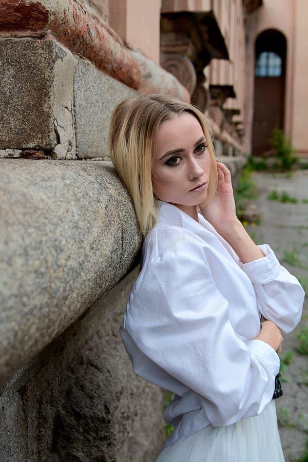 La femme du regard de mode Portrait moderne de jeune femme Jeune femme habill?e dans la jupe blanche et la chemise posant pr?s du images stock