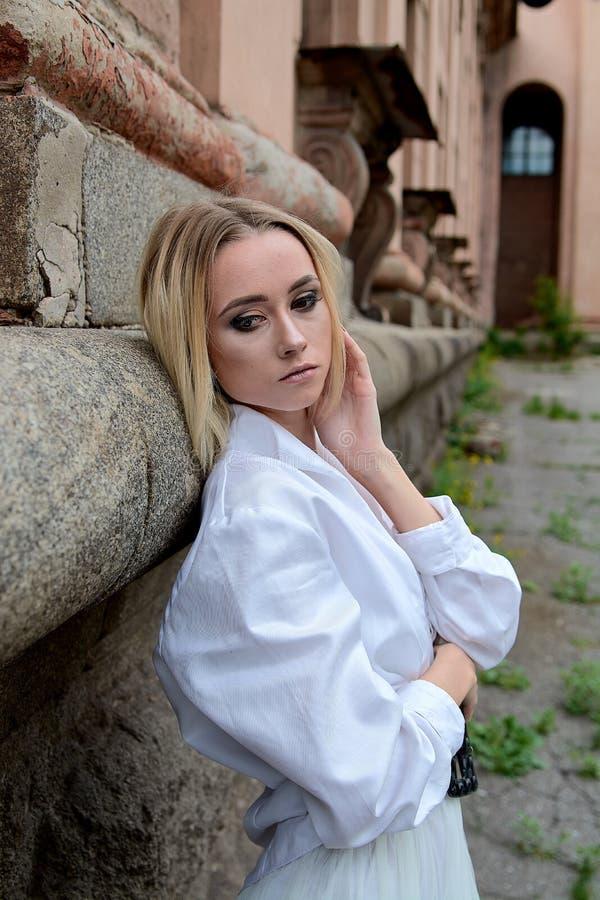 La femme du regard de mode Portrait moderne de jeune femme Jeune femme habill?e dans la jupe blanche et la chemise posant pr?s du photos stock