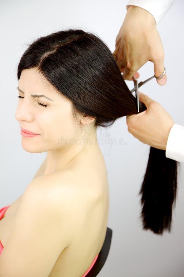 La femme a effrayé au sujet d'obtenir le long coupeur de cheveux pour la nouvelle coiffure images libres de droits