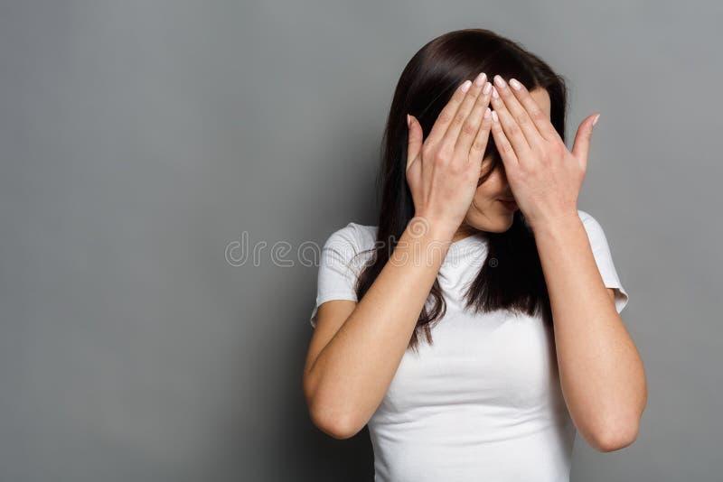 La femme effrayée que la bâche observe avec des mains, ne voient aucun mal image stock