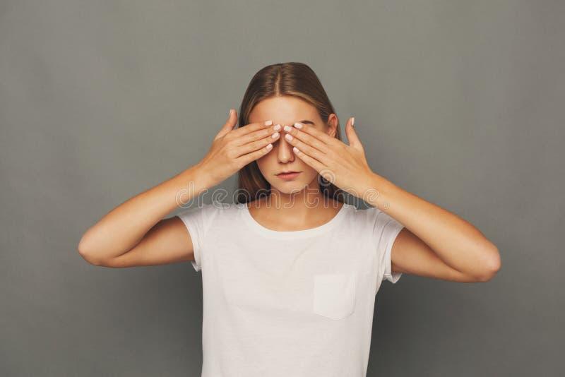 La femme effrayée que la bâche observe avec des mains, ne voient aucun mal photo libre de droits