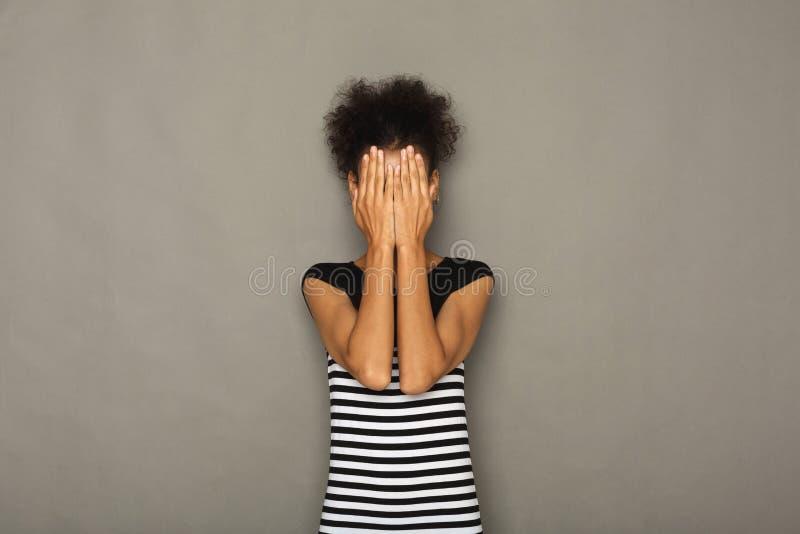 La femme effrayée que la bâche observe avec des mains, ne voient aucun mal images libres de droits