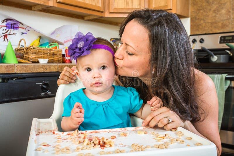 La femme embrasse le bébé dans la cuisine images stock