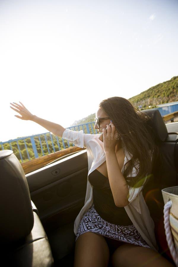 La femme emploie le téléphone portable et l'emplacement dans le cabriolet au jour d'été images stock