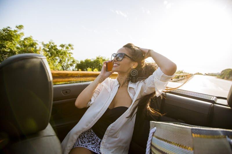 La femme emploie le téléphone portable et l'emplacement dans le cabriolet au jour d'été photographie stock
