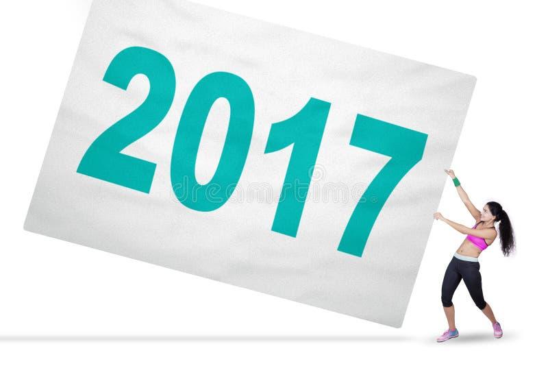 La femme en bonne santé tire la bannière avec 2017 photos stock