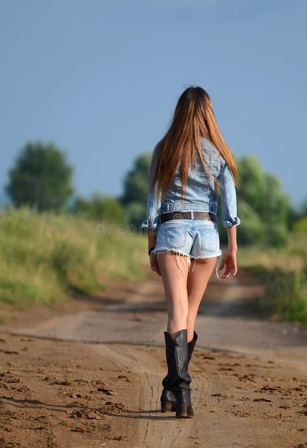 La femme en bref sur la route images stock