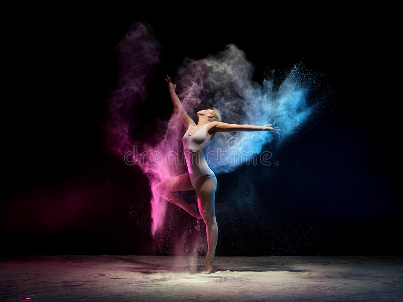 La femme en nuage de poussière de couleur s'étire avec élégance image libre de droits