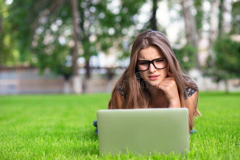 La femme en verres utilisant l'ordinateur portable a reçu un mauvais message sur le PC dehors photos stock