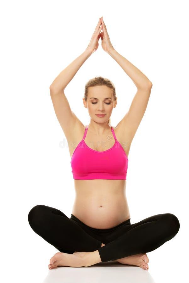 La femme enceinte détendent faisant le yoga images libres de droits
