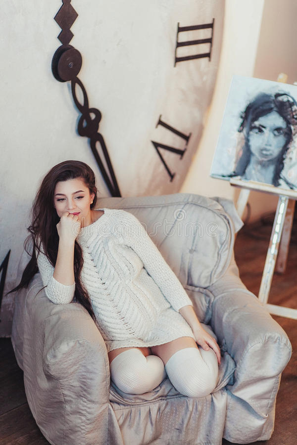 La femme enceinte de jeunes dans un chandail confortable s'assied dans une chaise Grande horloge à l'arrière-plan image stock