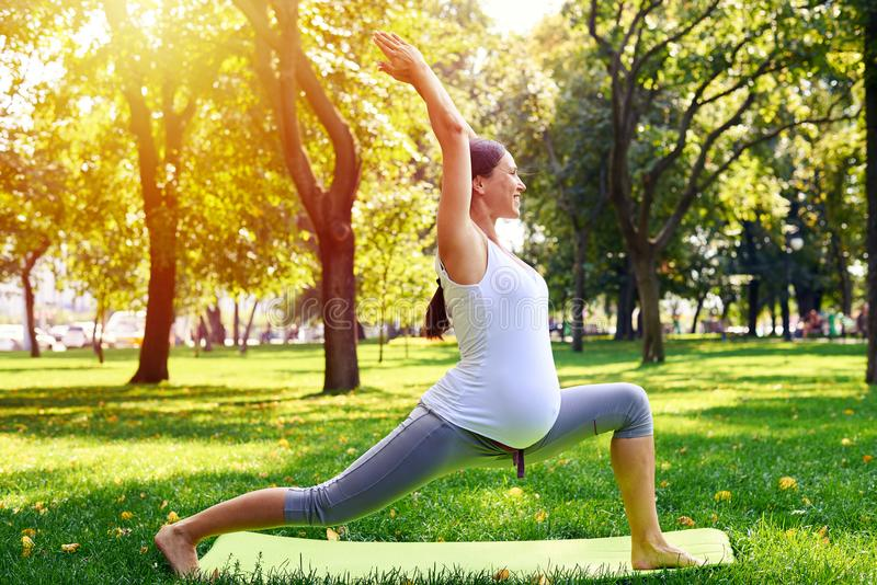 La femme enceinte de positif méditant dans le yoga posent dehors image stock