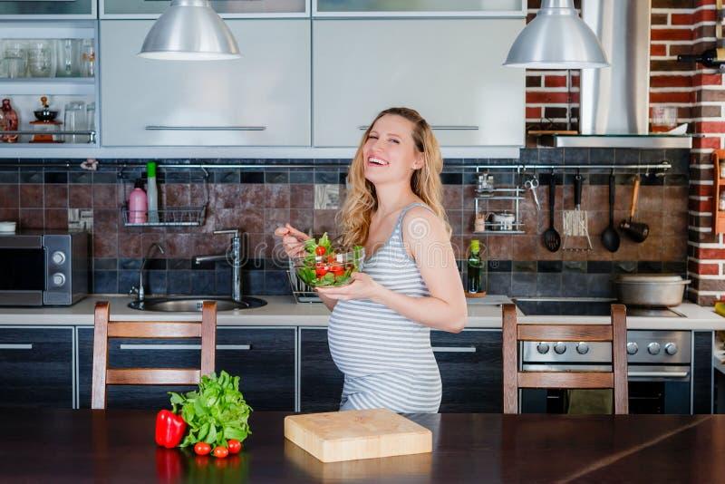 La femme enceinte de sourire dans la cuisine mange de la salade végétale images libres de droits
