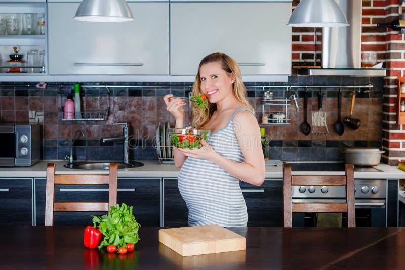 La femme enceinte de sourire dans la cuisine mange des conserves au vinaigre image libre de droits