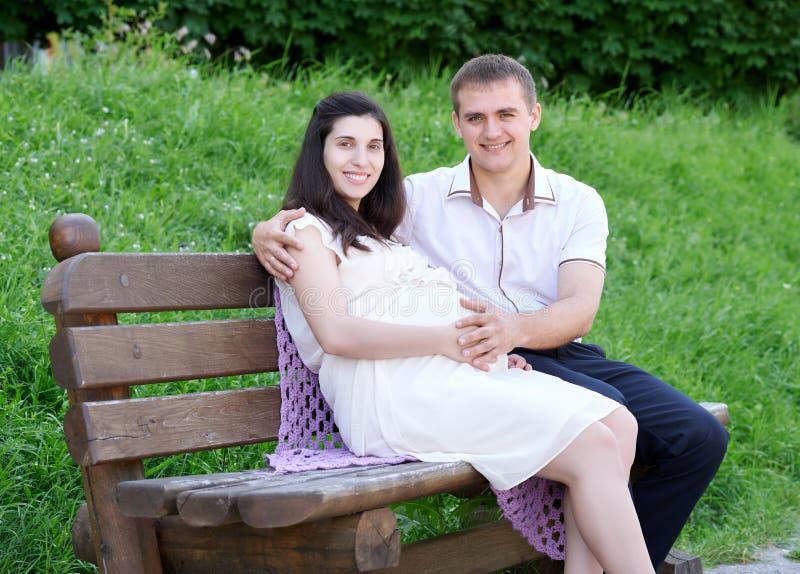 La femme enceinte et le mari sur la famille extérieure et heureuse, couple dans la ville se garent, saison d'été, herbe verte et  images libres de droits