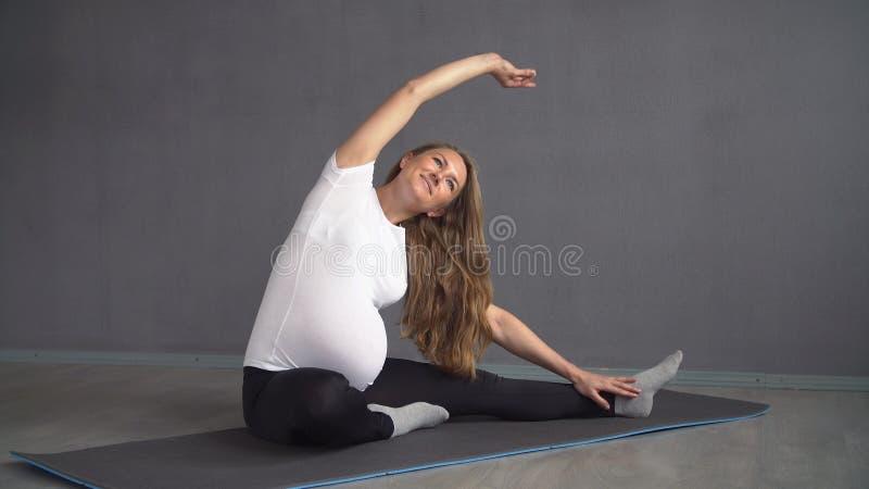La femme enceinte faisant la respiration s'exerce tout en se reposant sur les genoux yoga de pratique de fille photographie stock libre de droits