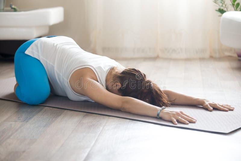 La femme enceinte faisant le yoga prénatal d'enfant posent à la maison images libres de droits