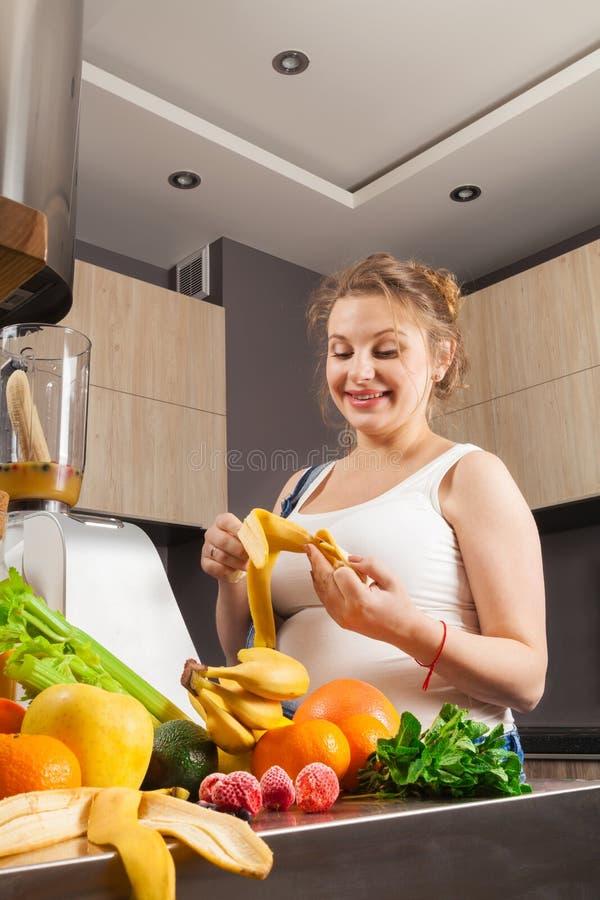 La femme enceinte fait un smoothie de fruit pour elle-même et son enfant dans la cuisine images libres de droits