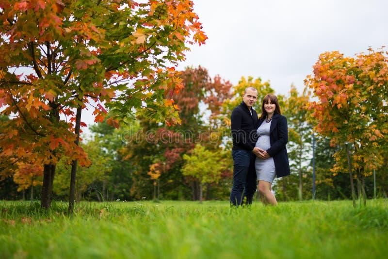 La femme enceinte heureuse et son mari en automne se garent photos libres de droits