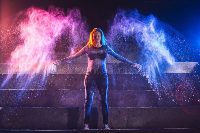La femme enceinte jette la poudre de couleur dans la forme des ailes d'ange photographie stock libre de droits
