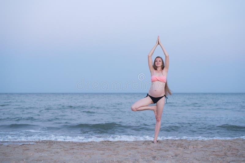 La femme enceinte médite sur la plage Pratique en mati?re de yoga Lumi?re molle de soir?e images stock